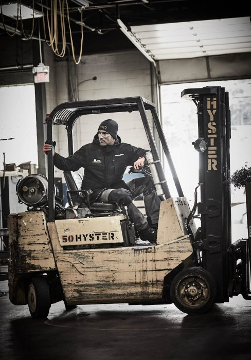 A man wearing work apparel operating a fork lift - work photography