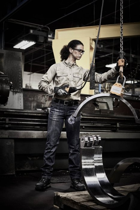 A woman operating heaving lifting tools with work apparel - work photography