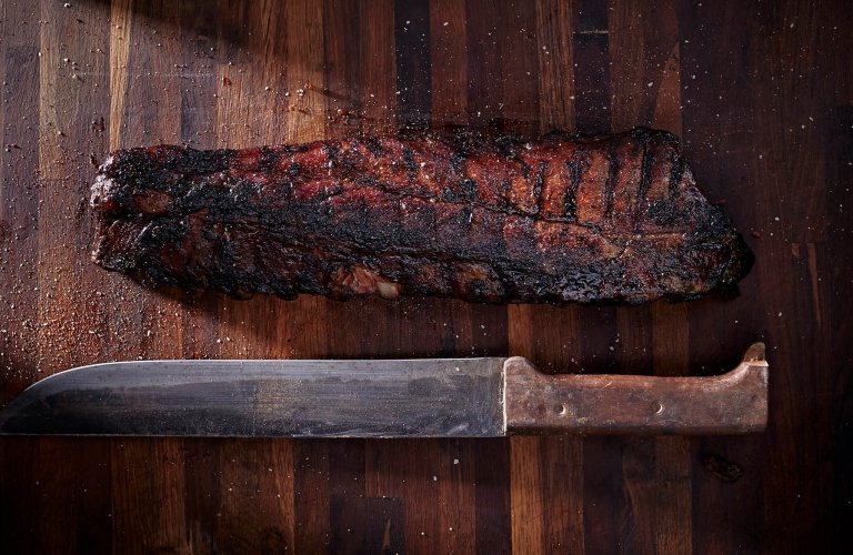 Smoked bbq ribs on a cutting board with knife - Food Photography