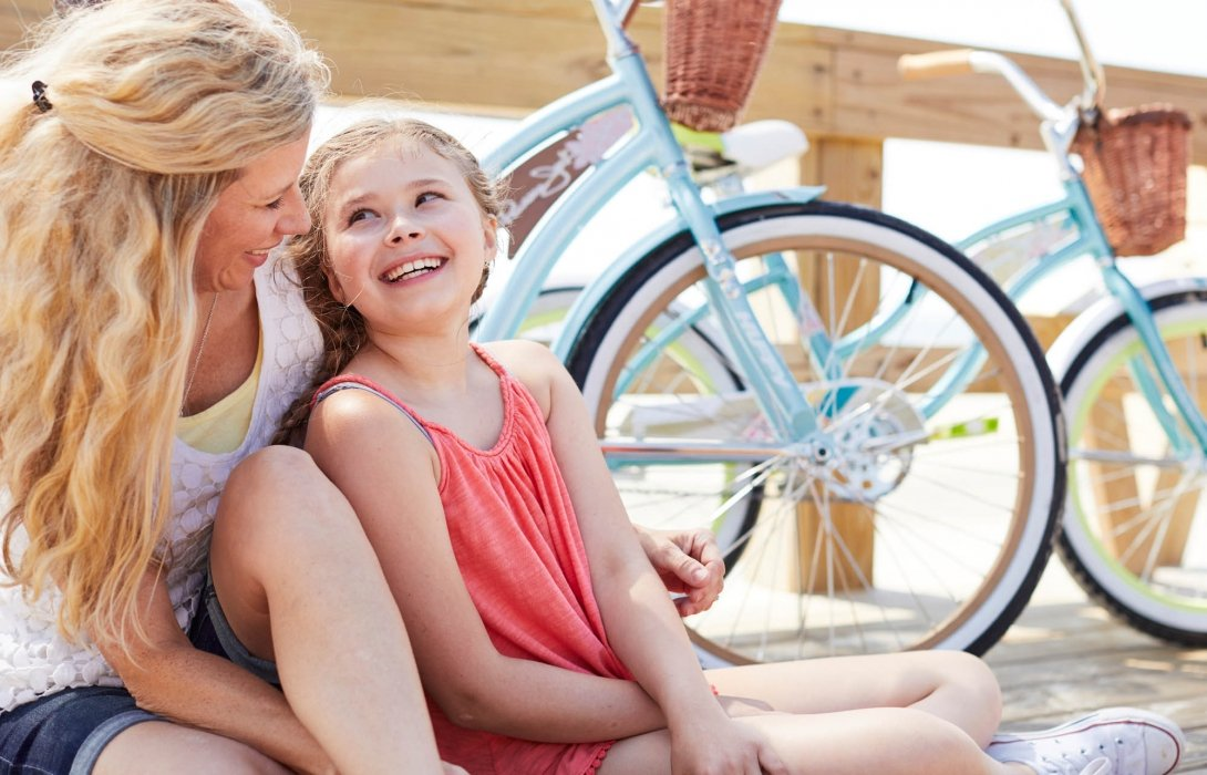 A young mom and daughter on a pier with bikes - lifestyle photography