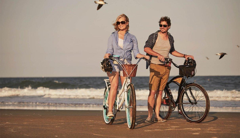 A couple on a beach walking their bikes - lifestyle photography