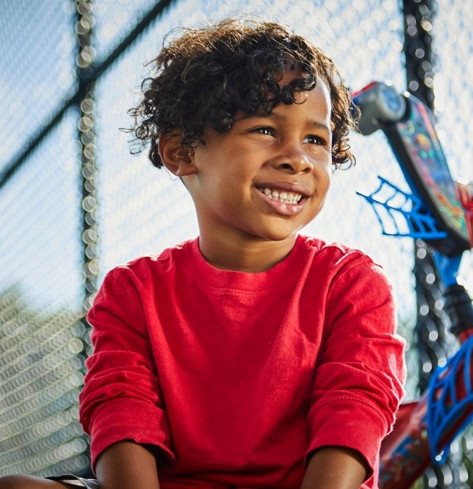 A portrait young boy smiling next to bike - lifestyle photography