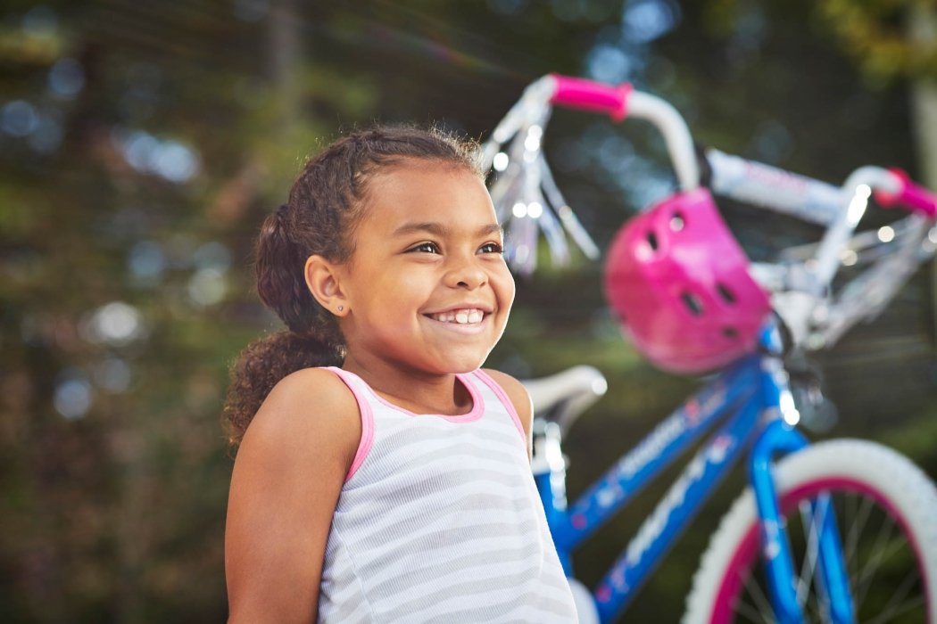 A young girl smiling next to her bike - lifestyle photography