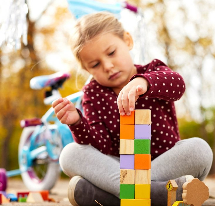 Girl playing with blocks next to bike in autumn with leaves - lifestyle photography