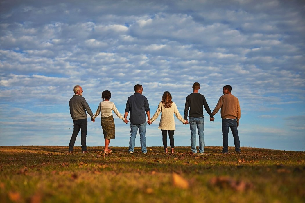 A group of six people holding hands in a field - lifestyle photography