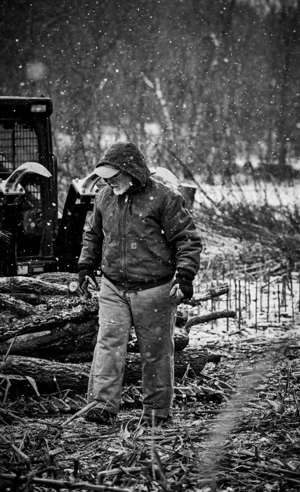 An old man working on a farm in winter walking through wood - lifestyle photography