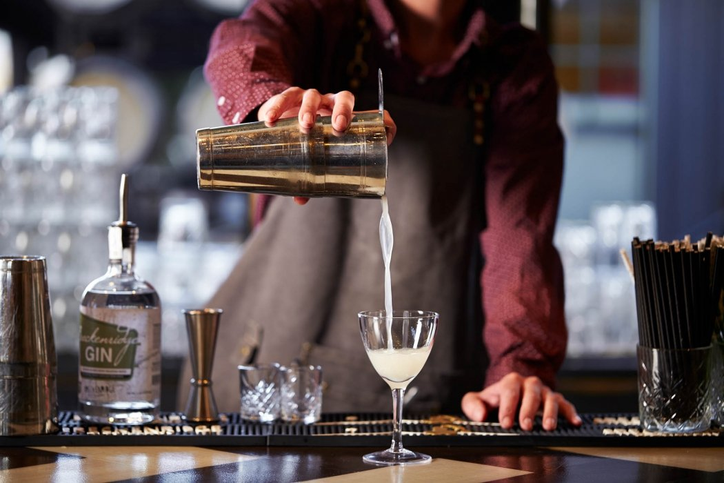 A bartender pouring cocktail at a bar - drink photography
