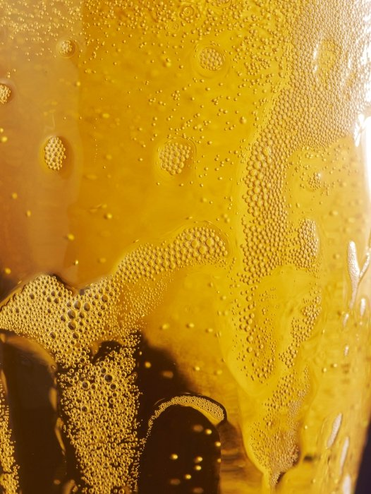Foaming beer bubbles close up and glass beer - drink photography
