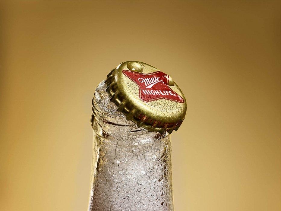 Miller high life beer bottle top foaming over in bottle - Drink Photography