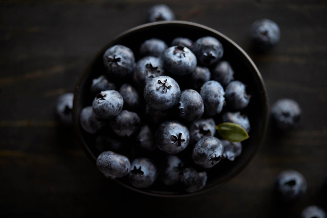 A bowl of perfect little blueberries on a dark surface - raw food photography