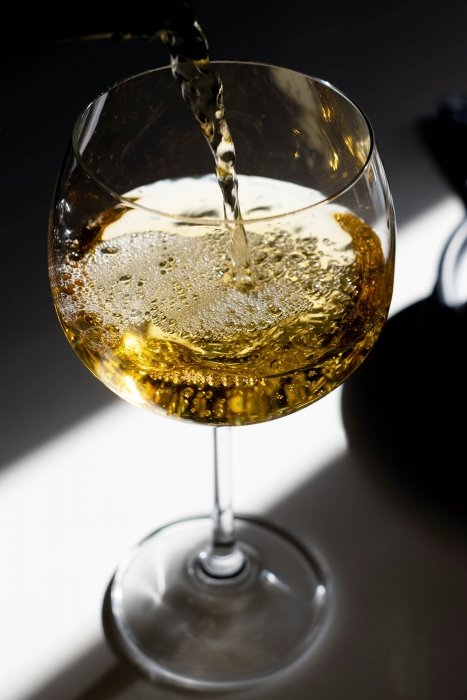 White Italian wine pouring with bold colors and dark photo - wine photography