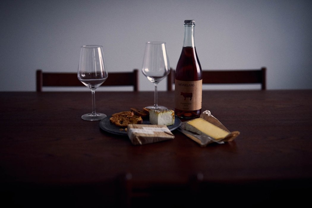 A dark fine wine Meinklang with cheese - wine photography