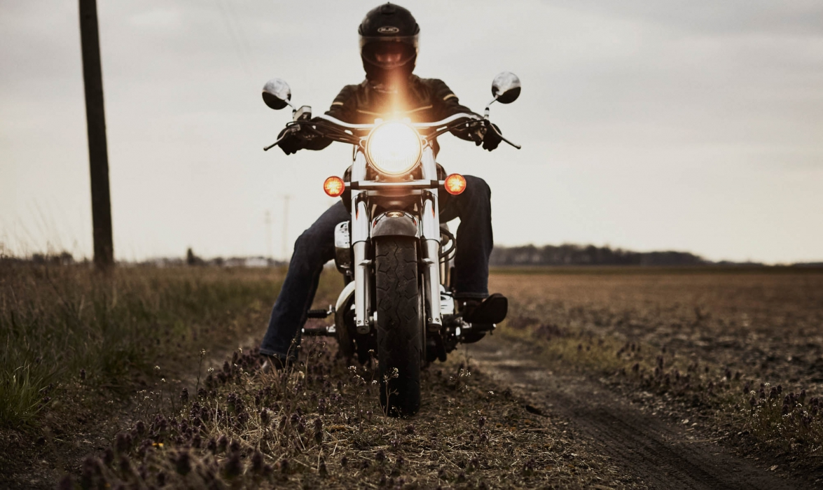 A biker on a motorcycle in a field - lifestyle photography