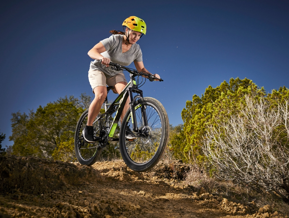 A woman with huffy bike riding through rugged terrain in air - product lifestyle photography