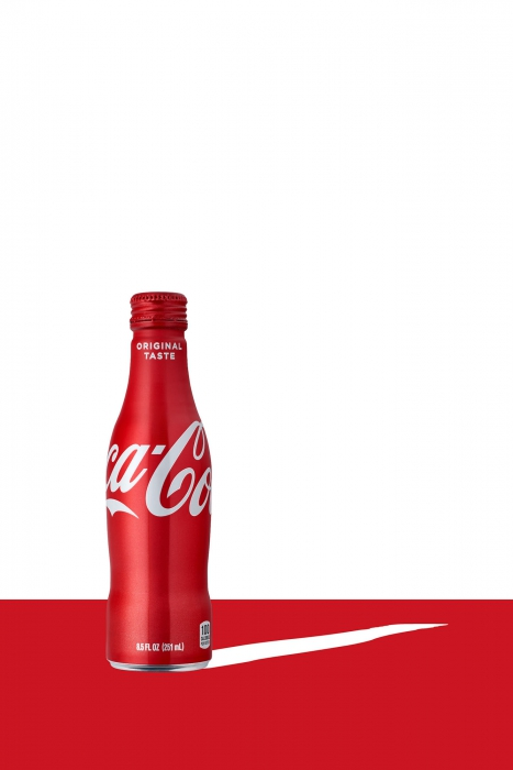 Coca cola bottle on clean red and white design - drink photography
