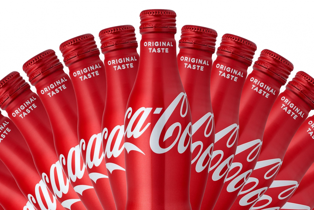 Multiple Coca cola bottles on clean red and white design - drink photography