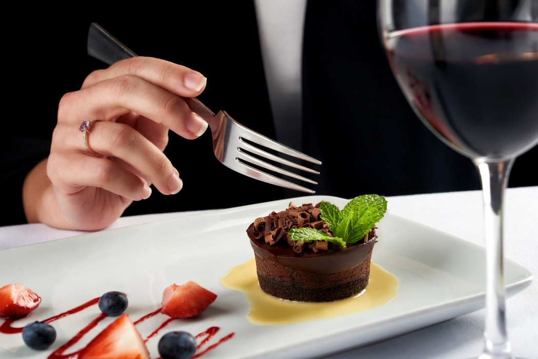 A hand with fork over a dark chocolate mint cake with berries and red wine - food photography