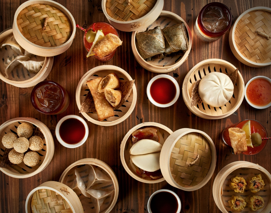 A flat lay of Asian food items in bamboo steamers - food photography
