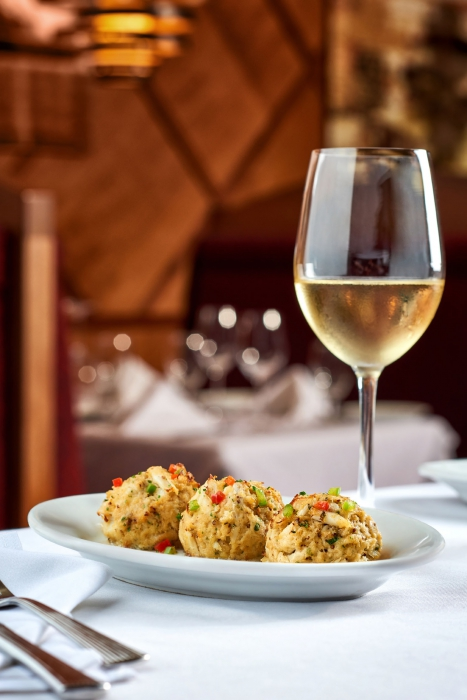 Three crab cakes and white wine high end - food photography
