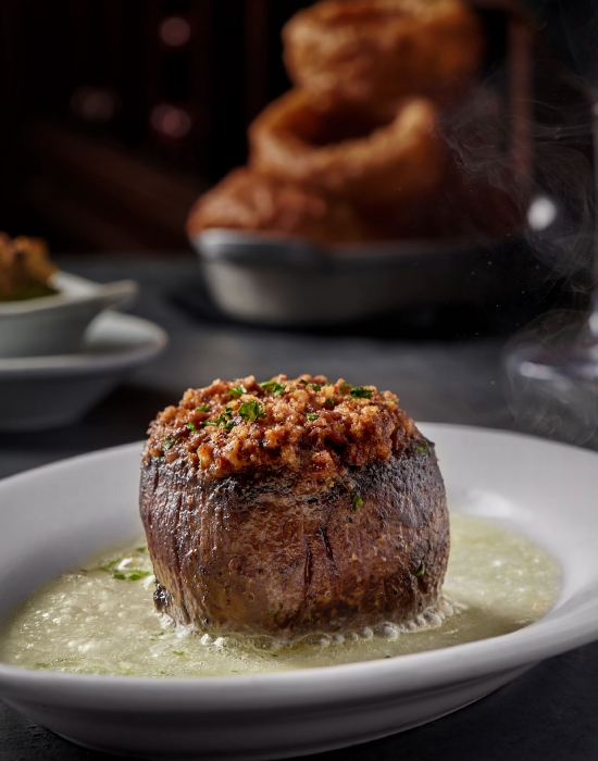 A steaming steak on a plate - food photography