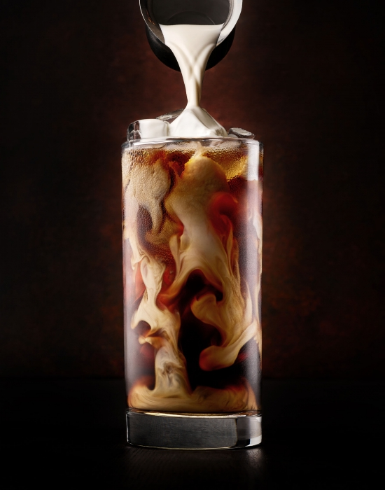 A creamy pour of cream over a glass of iced coffee- drink photography