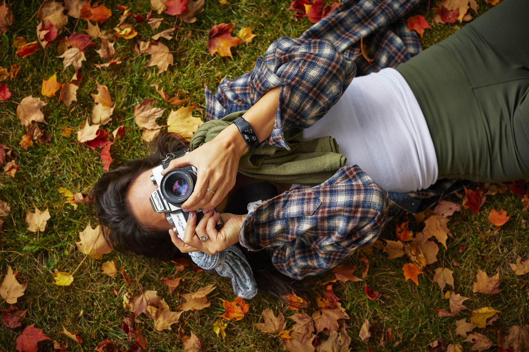 A young woman photographer laying on leaves and a grass - lifestyle photography