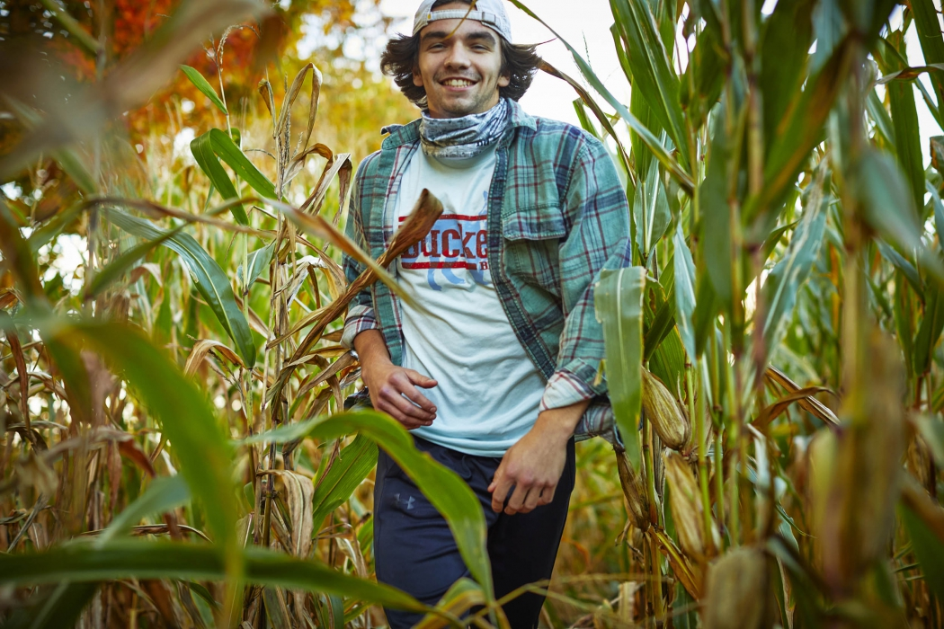 A young man walking through a field of corn - lifestyle photography