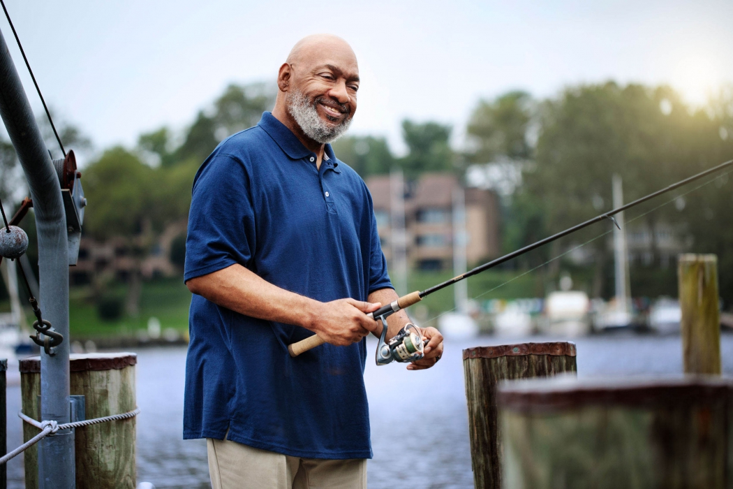 Portrait of a man with a fishing rod at a dock - portrait lifestyle photography
