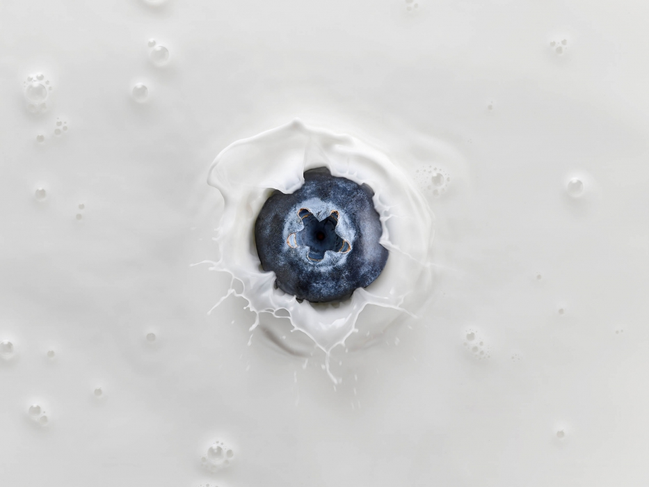 A blueberry splashing in milk - drink splash photography