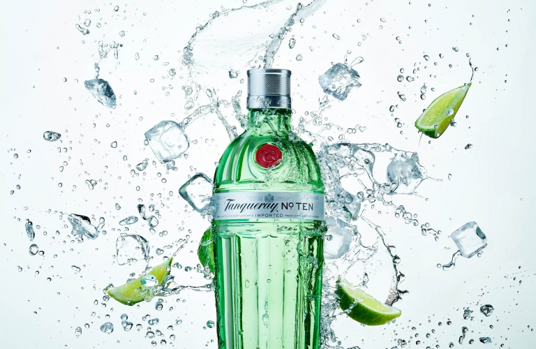 A bottle of tanqueray no ten with splashing water ice and limes - drink photography