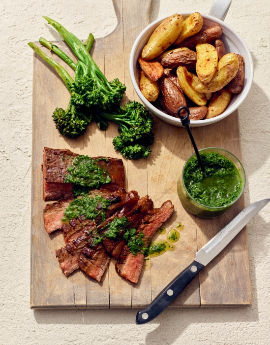 A cutting board with fresh cut steak, parsley sauce, roasted potatoes, and broccolini - food photography