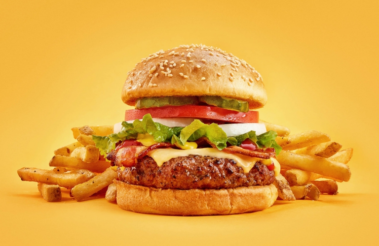 A golden cheese burger with fries on yellow background - food photography