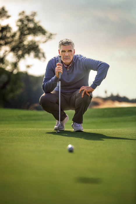 A man wearing KJUS golf apparel assessing a putt by a hole - lifestyle photography