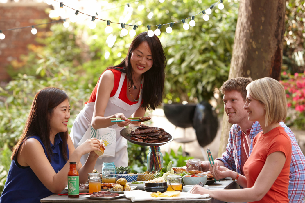 A group of friends enjoying a Korean BBQ cookout serving food - food lifestyle photography
